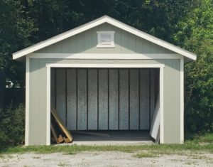 A 12 by 12 foot grey garage stands open and empty except for some wooden pallets.